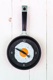 Clock like a pan with fried egg on the wooden Stock Images