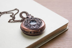 Clock locket. And book on wood texture Stock Photography