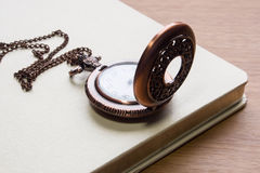 Clock locket. With white book on table Stock Images