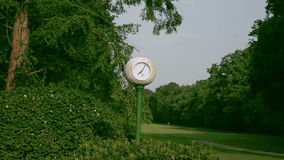 A clock looks like a golf ball at a golf course stock video footage