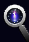 Clock in lupe on dark background Stock Photo