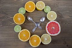Clock made of citrus fruits. On wooden background Stock Photos