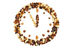 Clock made from nuts and raisins; isolated on whit Stock Photography