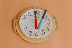 A clock made of piadina marks lunchtime. A white piadina forms a clock  with red and green hands remember that is an italian  product Royalty Free Stock Photo