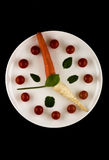 Clock made of vegetables on a white plate and black background. Royalty Free Stock Photos