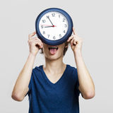 Clock man. Portrait of a young man holding a clock over a gray background Royalty Free Stock Image