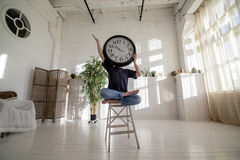 Clock man. Time concept. Clock man. A man sitting on a chair with a big clock covering his face in the loft. Time concept Royalty Free Stock Photos
