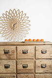 Clock and mandarins. Earthy homewares clock and mandarins on a storage buffet Royalty Free Stock Image