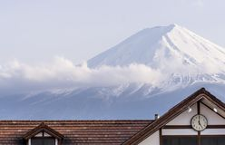 Clock that marks five o`clock with the snowy peak of Mount Fuji, Japan in the background stock image