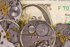 Clock mechanism with gears on dollar banknote. Clock mechanism with gears on background of US dollar banknote Stock Photography