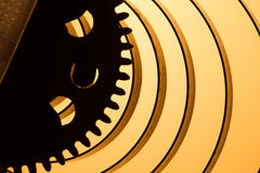 Clock mechanism high resolution. Focus on the central gears. Clock mechanism on gold background. Focus on the central gears. High resolution Stock Photos