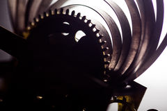 Clock mechanism high resolution. Focus on the central gears. Clock mechanism on grey background. Focus on the central gears. High resolution Stock Photography