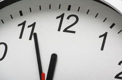 Clock at Midnight. Close up of a simple clock face with the hour and minute hands approaching midnight or twelve o'clock Royalty Free Stock Images