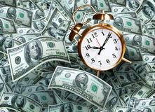 Clock on money. An alarm clock on a background of money with one hundred and fifty dollar bills. Concept for time is money royalty free stock image