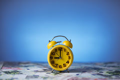 Clock and money. Yellow clock and money on the table on the blue background Stock Photos