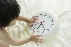 Clock in the Morning with Baby Boy up to catch it on the Couch. Royalty Free Stock Photo