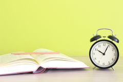 Clock near open book on green background Stock Image