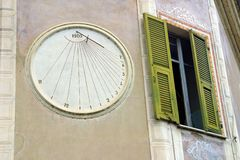 Clock Next to Window. Sun dail clock on building next to window with green shutters Stock Photos