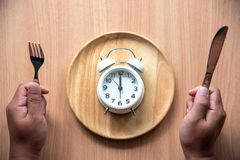The clock is at 12:00 noon for lunch in a wooden dish. The clock is at 12:00 noon for lunch in a wooden dish stock photos