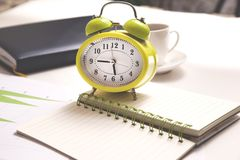 Clock on notepad and coffee on desk royalty free stock images