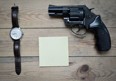 Clock, a notepad and  revolver Royalty Free Stock Images