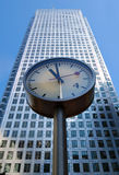 Clock and office building. A clock tower in front of a tall office building Royalty Free Stock Photography