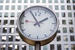 Clock with office windows. In the background Stock Images