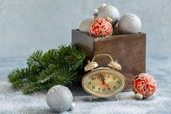 Clock and an old box with Christmas balls. stock photo
