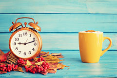 Clock over autumn leafs Royalty Free Stock Images