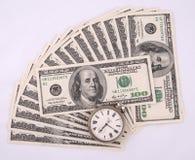 Clock over heap of money Stock Photo