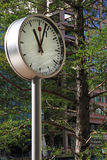 Clock in Park at Canary Wharf. A public clock in a peaceful park in the busy financial district of Canary Wharf, London. Focus on clock face, with trees and Stock Image