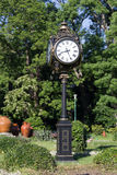 Clock in a park, in the spring. Clock in a public park, with lots of vegetation, in the spring stock photo