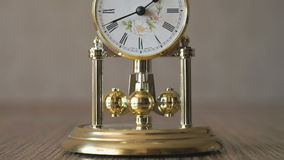 Clock with a pendulum in a form of rotating balls stock footage