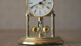 Clock with a pendulum in a form of rotating balls stock video