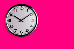 Clock on pink. Smiling clock on vivid pink wall reads ten past ten with copy space Royalty Free Stock Photo