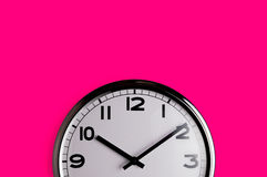 Clock on pink. Smiling clock on vivid pink wall reads ten past ten with copy space Royalty Free Stock Photos