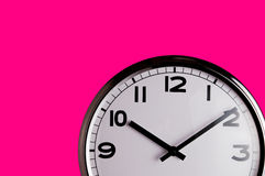Clock on pink detail. Smiling clock on vivid pink wall reads ten past ten with copy space Stock Image