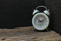 Clock placed on an old wooden floor, black backdrop.  royalty free stock photography