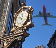Clock and Plane. A view of a clock in the city at 10:00 am with an airplane flying overhead Stock Photos