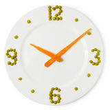 Clock from plate, carrots and green peas Royalty Free Stock Photos