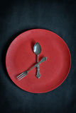Clock with red plate, spoon and fork Royalty Free Stock Photos