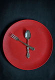 Clock with red plate, spoon and fork Royalty Free Stock Photo