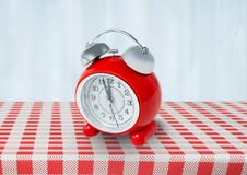 Clock on red tablecloth. Digital composite of Clock on red tablecloth Stock Photo