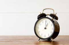 A clock. Retro alarm clock and white wooden wall background Royalty Free Stock Images