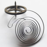 Clock's Spring and gyroscope. A spring and a gyroscope , coming from an old clock in a squared color compo Stock Photos