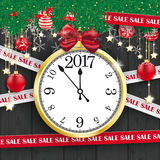 Clock 2017 Sale Lines Christmas Black Wood. Sale lines with twigs, card and baubles and clock on the black wooden background Royalty Free Stock Images