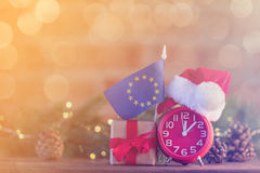 Clock with Santa Claus hat near a Europe Union flag Royalty Free Stock Image