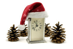 Clock with Santa hat and pine cones Stock Photography