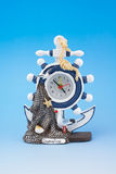 Clock - sea attributes. Clock souvenir from Italy on blue background Royalty Free Stock Photo