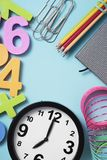 School supplies and clock at seven. A clock at seven, some pencil crayon of different colors, a notepad, some paper clips and some three-dimensional numbers of Stock Photos